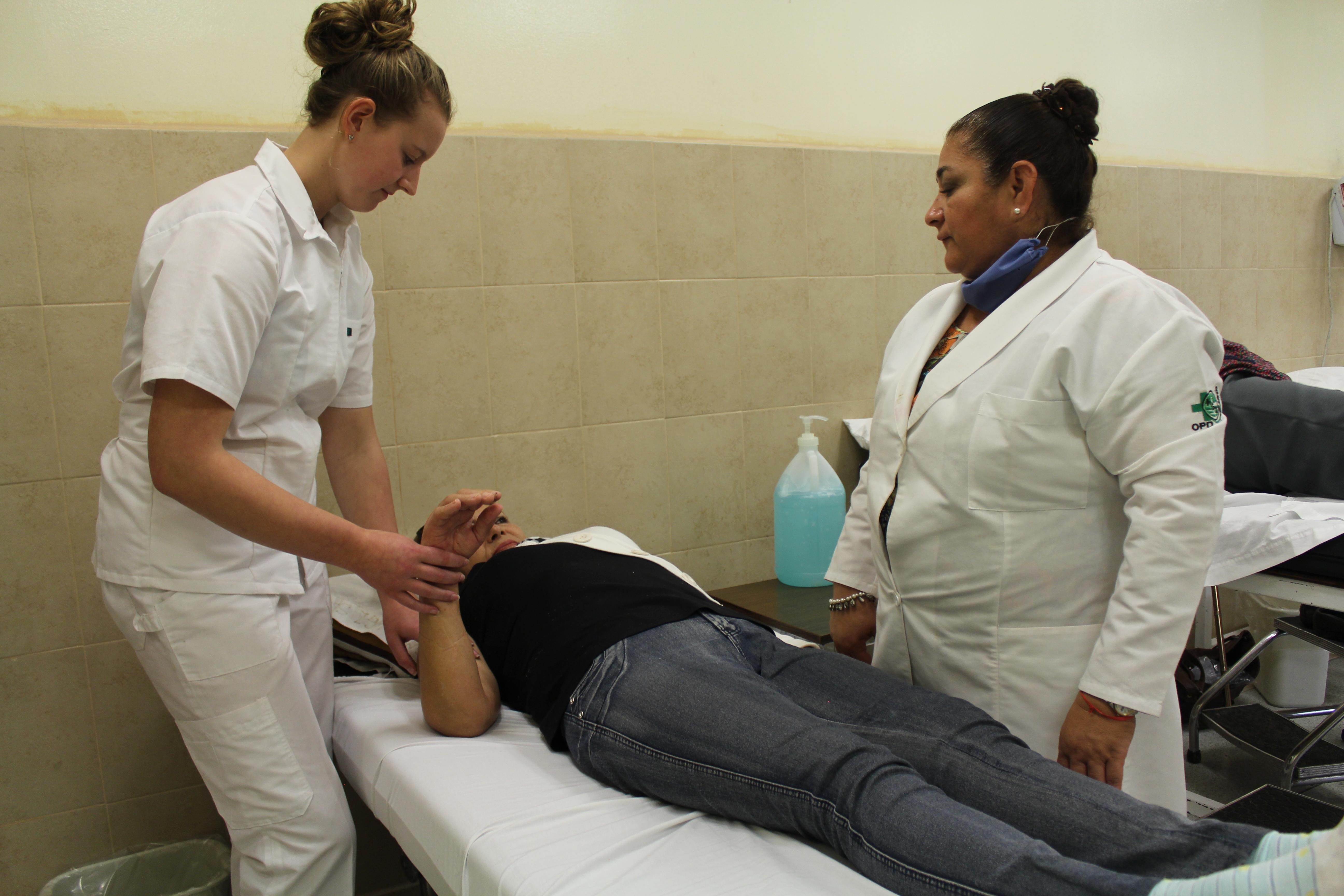 A female intern from Projects Abroad is pictured assisting a local doctor treating a patient whilst on her physiotherapy internship in Mexico.